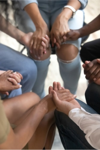 Circle of people sitting together holding hands