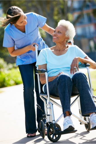 Caregiver pushing wheelchair with a woman in it in a park both are smiling