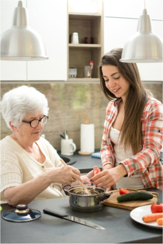 Woman assisting senior woman with cooking
