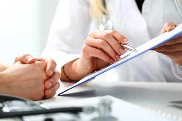 Doctor's hand holding silver pen and sharing a document
