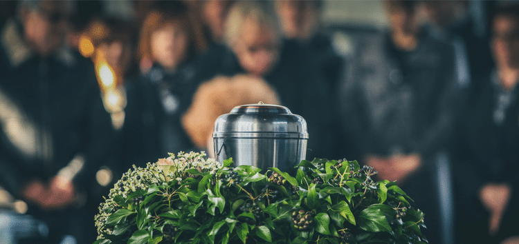 Mourners at a funeral with cremation urn in forefront